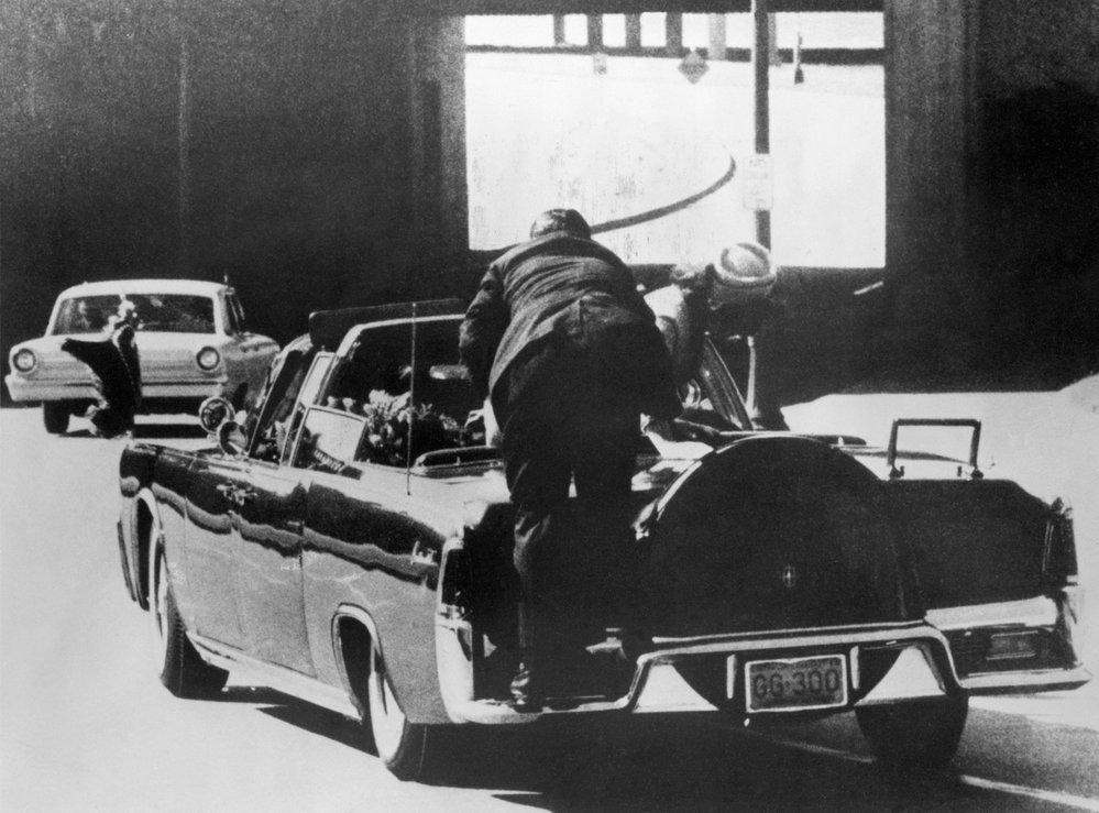 Bodyguard se sklání nad tělem mrtvého prezidenta, tomu však již pomoci nedokázal. Kennedy zemřel poté v nemocnici.