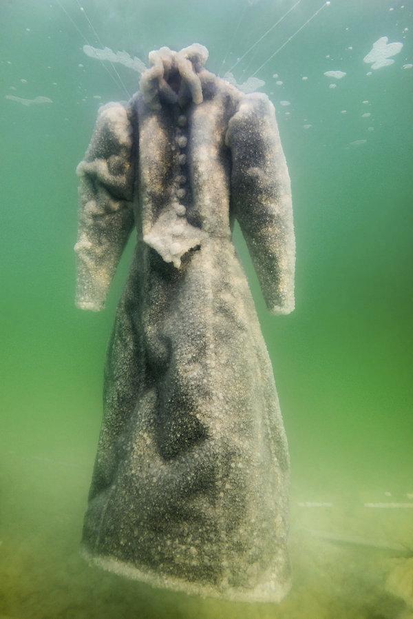 """""""Leahiny černé šaty se pod vodou postupně vlivem soli měnily. Každým dnem je alchymie moře dále měnila ze symbolu šílenství na to, co měly vždy být – svatební šaty,"""" uvedla Sigalit Landau pro muzeum Marlborough v Londýně, kde je výsledek experimentu vystaven v expozici Solná nevěsta."""
