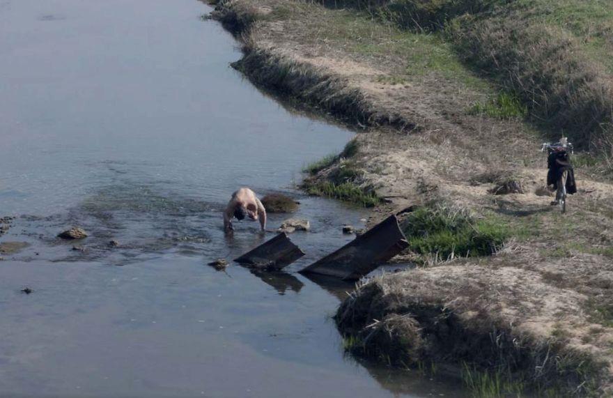 Muž, který se koupe v řece kousek za městem.