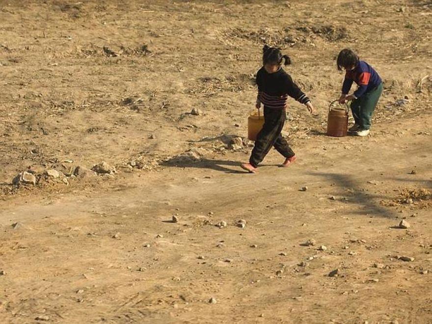 Děti nesoucí vodu z nejbližší studny.