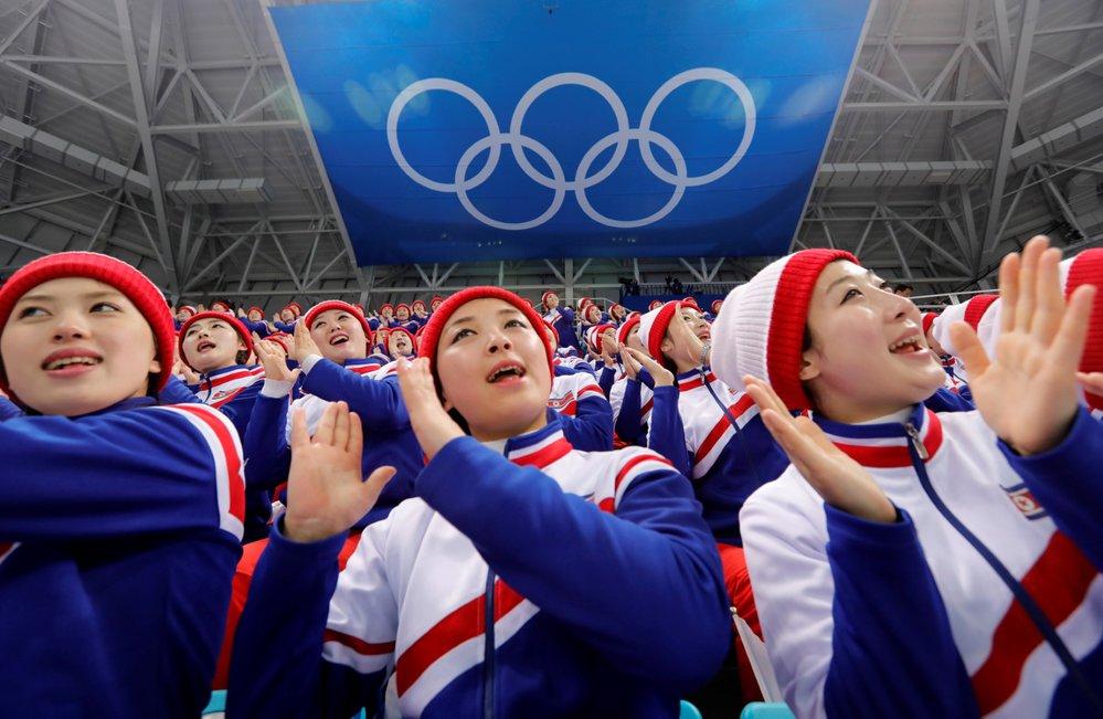 Severokorejské fanynky na tribunách sborově mávají, zpívají a tleskají