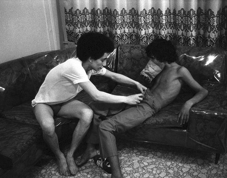 Šestnáctiletý chlapec živící se prostitucí čichá lepidlo, zatímco ho jeho starší známý svléká. (New York, 1979)