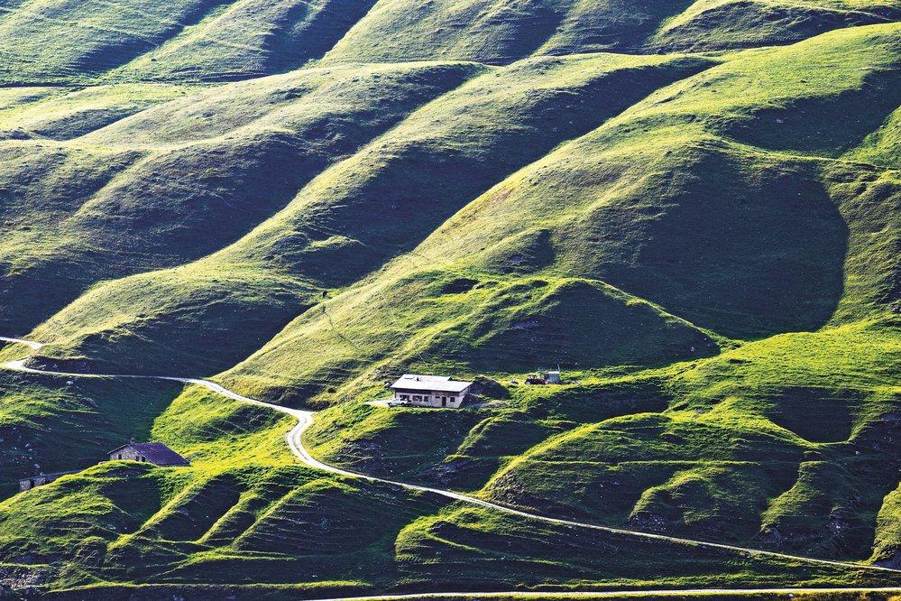 Pohled nasvahy nafrancouzské straně Velkého Svatobernardského průsmyku. Zelené svahy odkryje sníh během léta jen nakrátko. Pasou se tu stáda krav, zjejichž mléka se pak vyrábí namalých farmách skvělý sýr Beaufort.