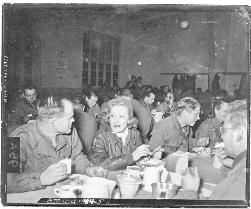 Filmová hvězda Marlene Dietrichová u jídla s vojáky během turné USO (U.S. Army Signal Corps)