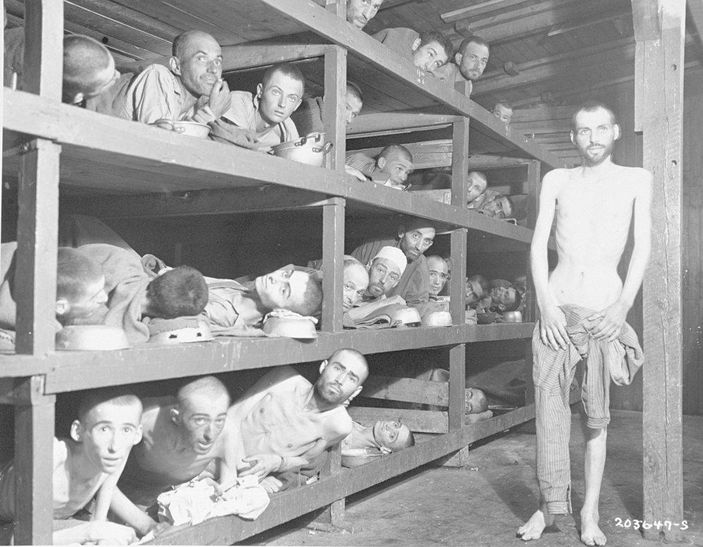 Osvobození vězni v Buchenwaldu hledí z dřevěných paland. Budoucí držitel Nobelovy ceny za mír Elie Wiesel je ve druhé řadě paland sedmý zleva u vertikálního trámu. (United States Holocaust Memorial Museum)