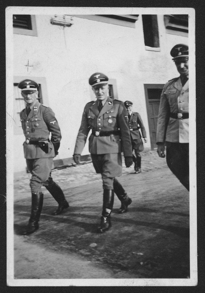 Fotorekonstrukce obličeje Ernsta Gerkeho při jeho návštěvě v Terezíně v roce 1942. Na snímku je zachycen při inspekci společně s H. U. Geschkem (uprostřed) a H. Jöckelem (vpravo). Snímek měl podpořit tvrzení československých vyšetřovatelů o jasném povědomí Gerkeho o řádu a zločinech v policejní věznici.