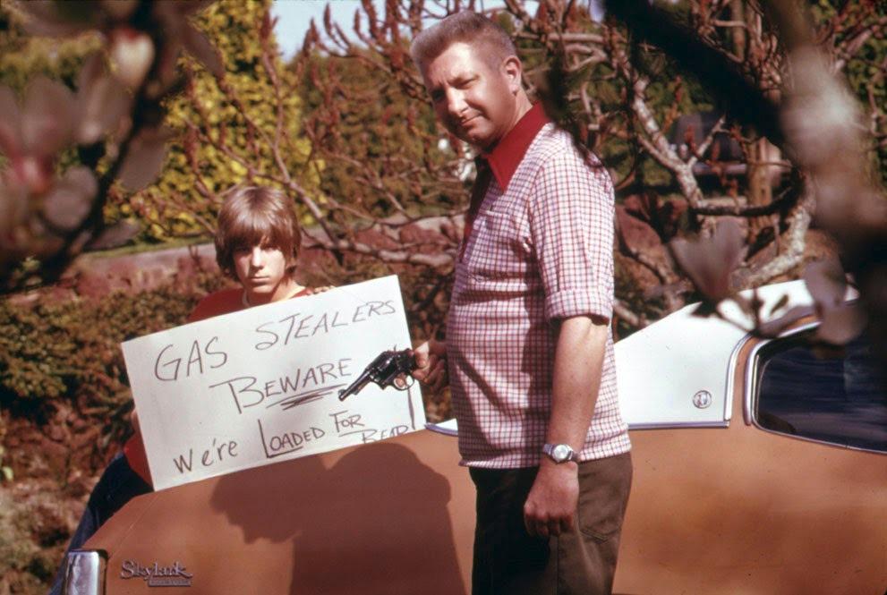 Během ropné krize se zloději často uchylovali k vykrádání nádrží. Otec se synem na fotografii případné zájemce o jejich benzín jasně varují.