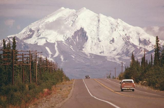 Glen Highway na Aljašce. V pozadí Mount Drum. Kůly po stranách vozovky mezi oběma vozy značí, kudy povede Aljašský ropovod (srpen, 1974).