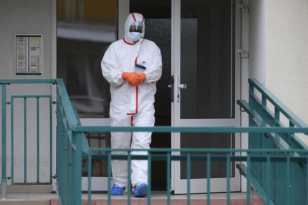 Pracovník zdravotnické záchranné služby v ochranném obleku nese 6. března 2020 nádobu s biologickým materiálem odebraným v jedné z domácností v Praze. V hlavním městě začali zdravotníci odebírat vzorky pro potvrzení nákazy novým typem koronaviru v domovech lidí, které k testu určila krajská hygienická stanice. Vyjíždí k nim sestra či lékař v odběrové sanitce.