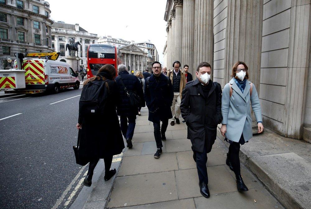 Lidé s ochrannými rouškami v Londýně (11.3.2020)