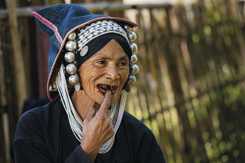 Žena z kmene Akha žijící v horské vesnici nedaleko Kengtungu poukazuje na své načernalé zuby po dlouholetém žvýkání betelu