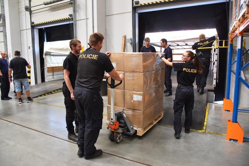 Česká pošta společně s hasiči a policíí distribuuje roušky a respirátory.