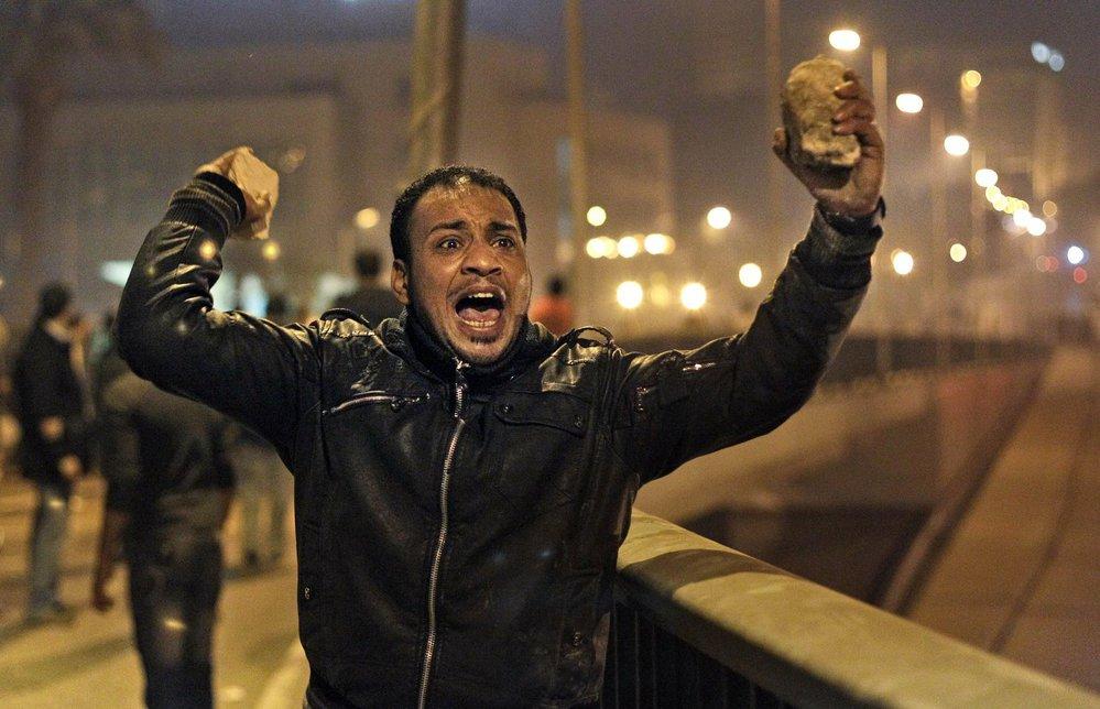 Demonstrant s dlažební kostkou v ruce.