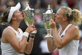 Barbora Krejčíková s Kateřinou Siniakovou líbají své poháry pro vítězky wimbledonské čtyřhry