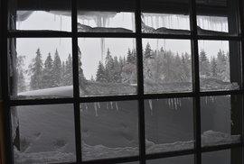 Pohled z okna meteorologické stanice. Sníh je všude, kam se člověk podívá.