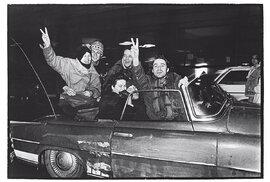 """""""Nejsem si jistý, zda to je vpondělí, nebo vúterý po17. listopadu 1989,"""" datuje dobu vzniku fotografie Jan Mihaliček. Nasnímku zachyceném před kavárnou Slavia oslavuje čerstvě nabytou svobodu skupina přátel vestaré felicii: zavolantem nepříliš viditelná majitelka automobilu, dnes interiérová designérka Alice Kovácsová, vepředu (sknírkem) sochař Jaroslav Róna, pod jeho ramenem režisér Tomáš Vorel, vedle manažerka skupiny Laura ajejí tygři Marie Šůchová, nad nimi tanečník achoreograf Petr Záveský avzadu nakapotě sedící Kateřina Lokvencová aPatrik Fejfar."""
