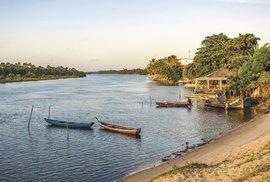 VBarreirinhas zapadá slunce kolem šesté aopuštěné čluny místních rybářů se pohupují naklidné hladině řeky Preguiça